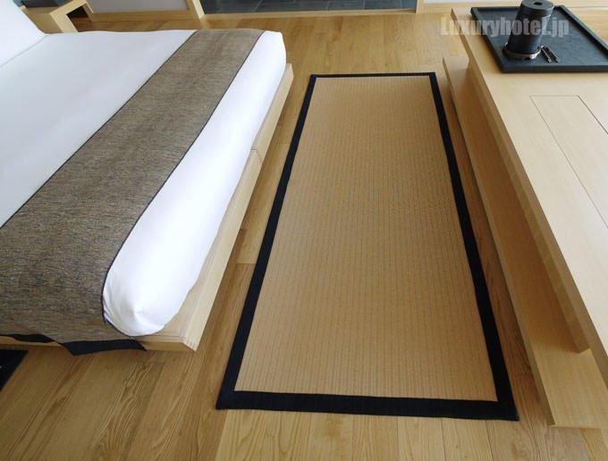 ベッドとミニバーの間には畳のように編まれたフロアマット
