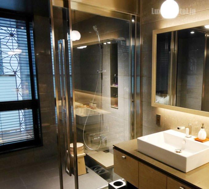 洗面台の左側にシャワールームとバスルームがある